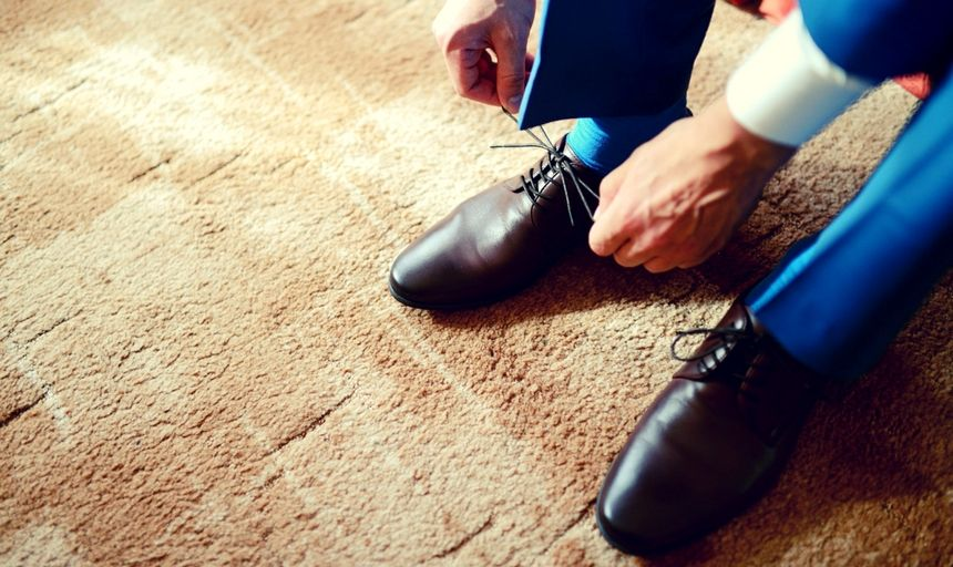 Man in blue suit with brown shoes tieing shoelaces
