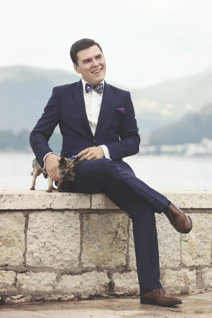 Man in navy suit with brown shoes sitting on a ledge with a dog