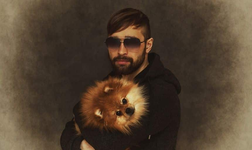 Man with beard and sunglasses holding a fluffy dog