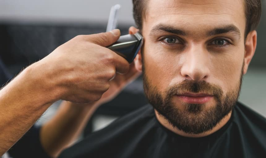 Bearded man looking directly at the camera and getting his sideburns tapered with clippers