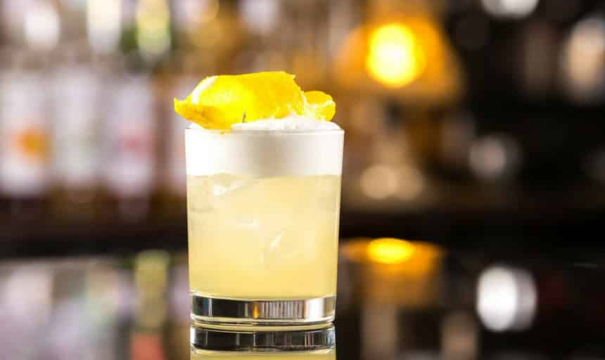 whiskey sour cocktail with bar in background