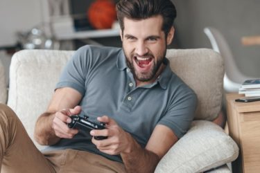 Handsome guy excited to be playing video games on the couch