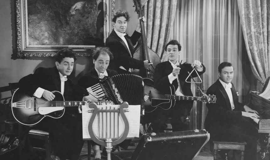 A band featuring guitar, accordian, drums, bass, triangle - vintage style in black and white