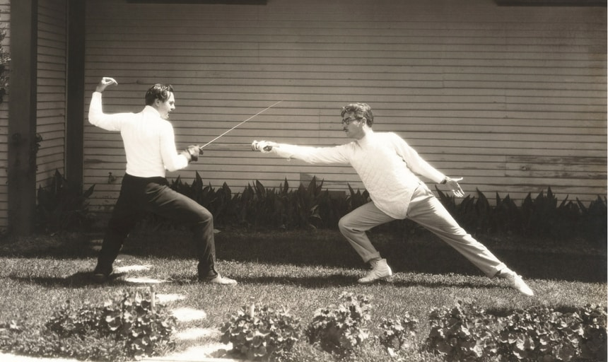 Black and white image of two men fencing - vintage style, one man being struck