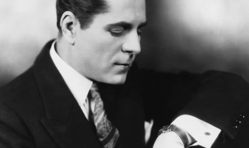 Business man looking at watch in suit - black and white vintage