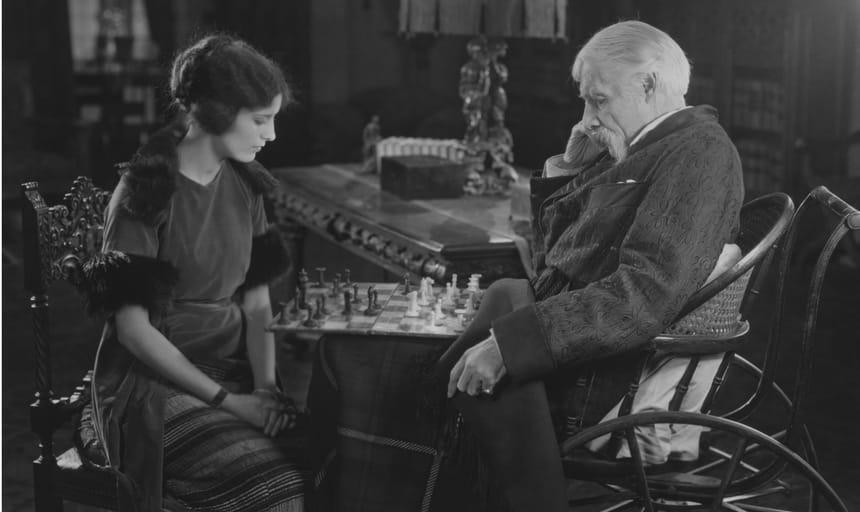 Elderly man and woman deep in thought playing chess - black and white vintage