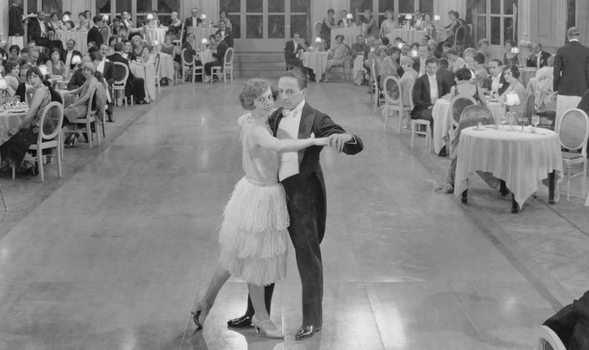 Man and woman ballroom dancing in the middle of the room with people watching at tables, black and white vintage