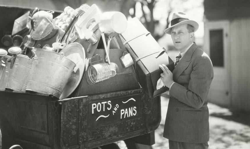 Man collecting pots and pans in a trailer - black and white