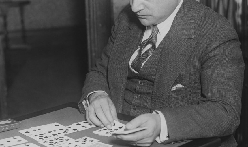 Man in suit playing solitaire - card game, black and white vintage