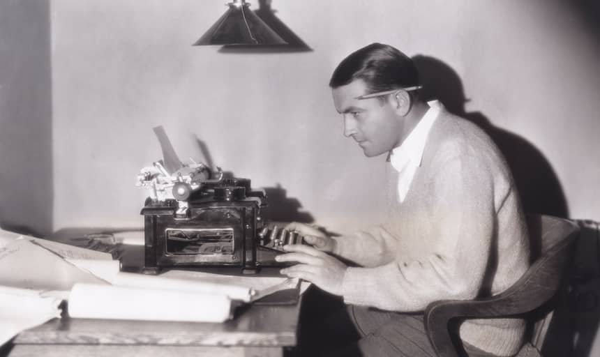 Man writing on a typewriter with pencil behind his ears - vintage in black and white