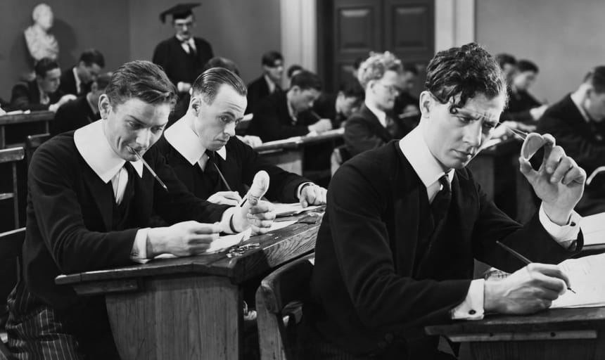 Men in class, one guy smiling, the other guy cheating - black and white, vintage style