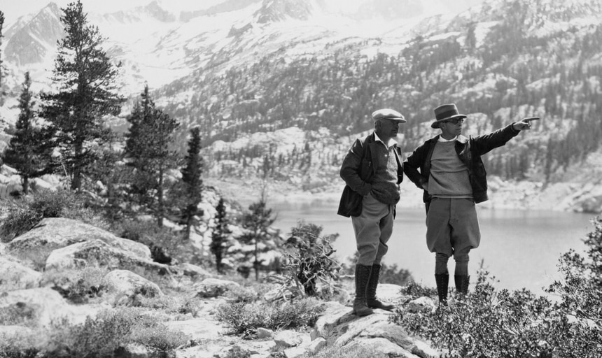 Two elderly men out hiking in the wilderness, one man pointing in the distance, in black and white