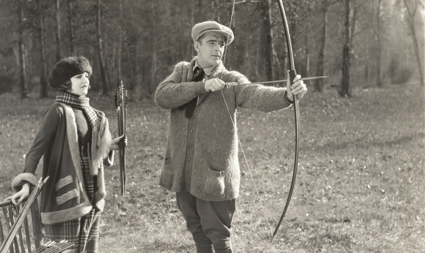 Vintage archery image, man drawing bow with woman watching