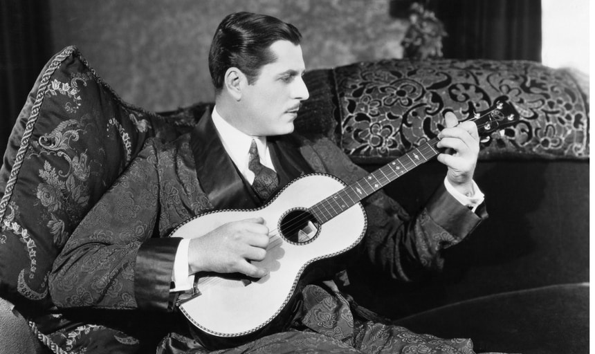 Vintage man playing an acoustic guitar in black and white in a robe