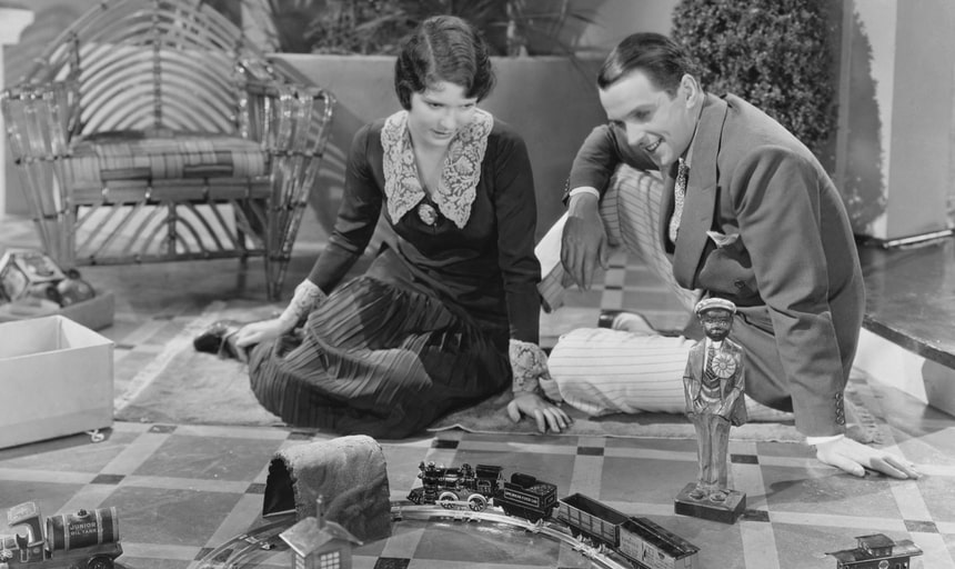 Young man and young lady playing with a train set - black and white vintage