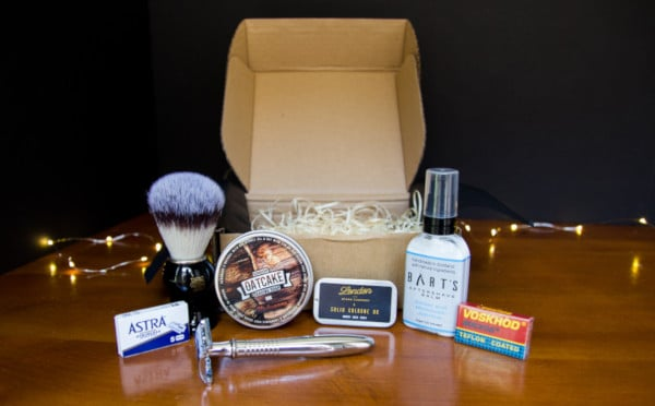The Personal Barber Subscription Box Opened on a Wooden Table with Lights in the Background