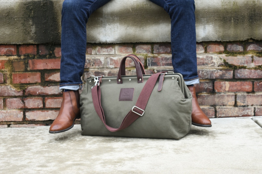 Bespoke Post Weekender Bag Outside Sitting At Feet of Model Wearing Jeans and Boots