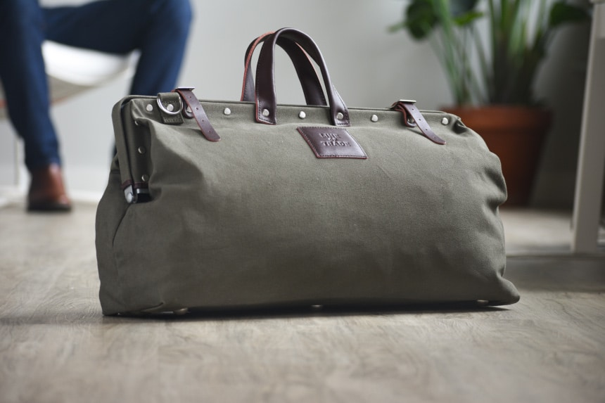 Close Up of Olive Bespoke Post Weekender Bag With Male Model in Background Inside Setting