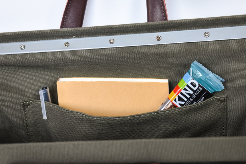 Close up of Inside of Bespoke Post Weekender Bag in Olive Including Protein Bar and Book and Pen in Pocket
