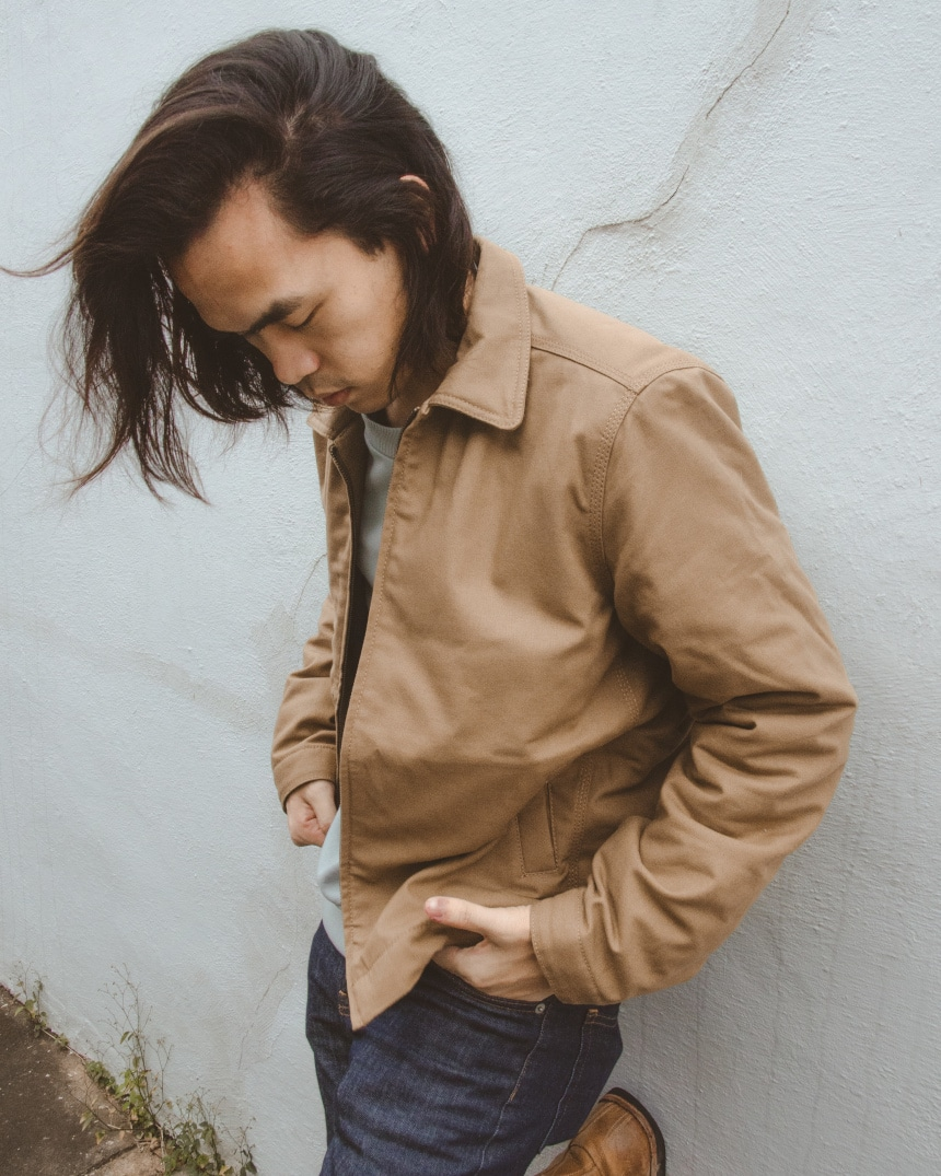 e02e59303c0 Male model leaning against a wall wearing Everlane Midweight Canvas Jacket,  Fleece Crew, and