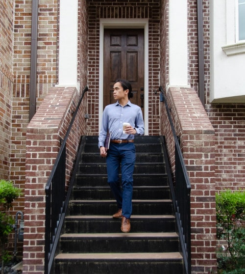 Model Wearing Mizzen+Main Beckett Dress Shirt While Walking Out of a House and holding coffee and a folder