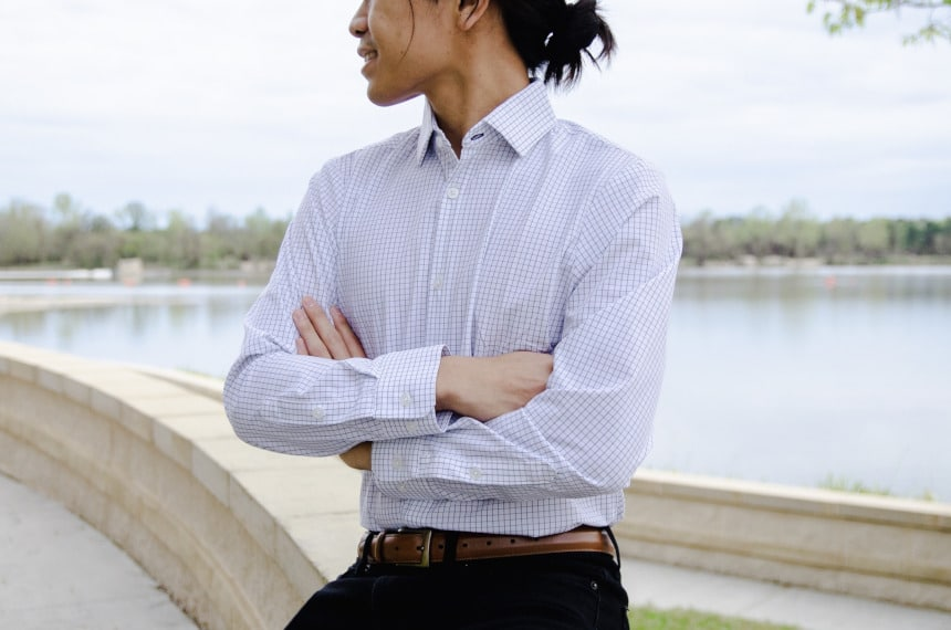 Model Wearing Mizzen+Main Kennedy Dress Shirt Sitting Down and Smiling While Crossing Hands