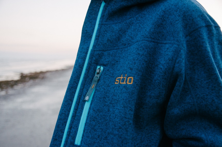 Close Up of Stio Logo on Wilcox Fleece Hoodie in Larkspur Blue on Model