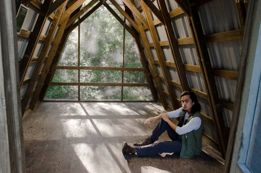 Male Model Wearing TravelSmith Voyager 15-Pocket Vest in Olive Inside of Cabin in Park And Looking at Camera