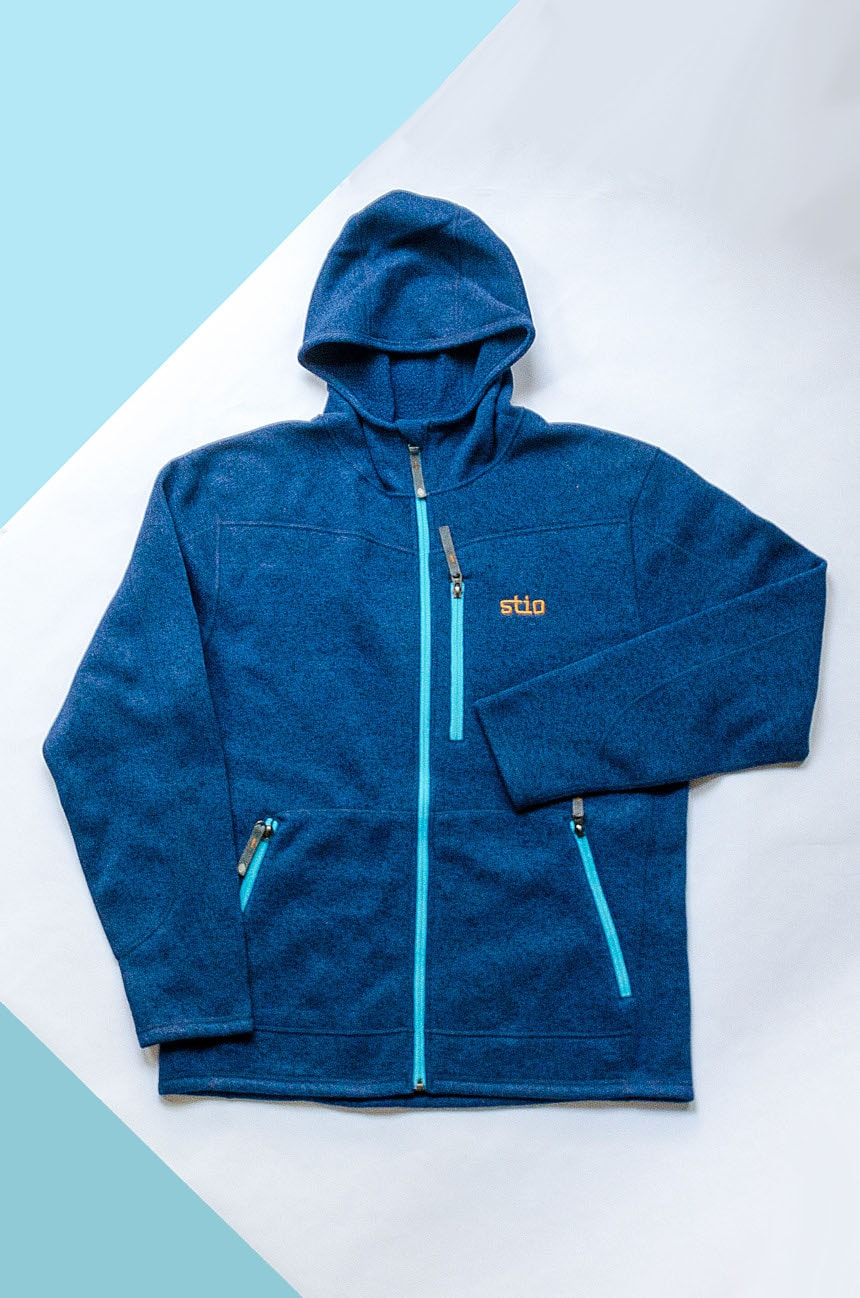 Stio Wilcox Fleece Hoodie in Larkspur Blue on Blue And White Paper Background