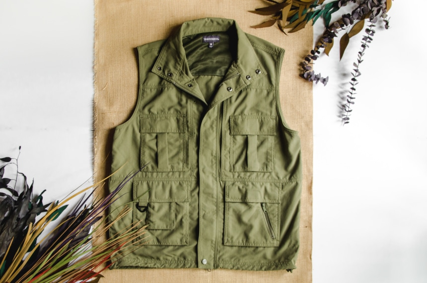 TravelSmith Voyager 15-Pocket Vest in Olive Sitting on Canvas Style Background with Leaves around
