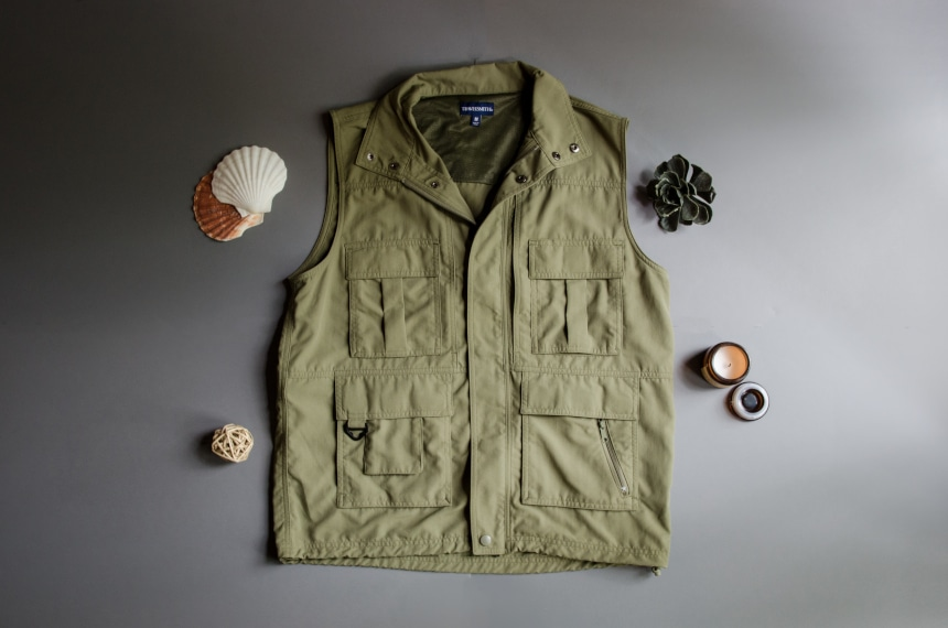 TravelSmith Voyager 15-Pocket Vest in Olive Sitting on Grey Background with Shells around