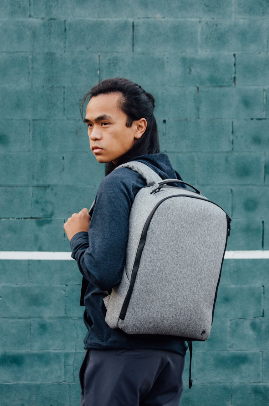 Model Carrying Public Rec Pro Pack On Shoulder And Looking Into Distance Against Aqua Wall