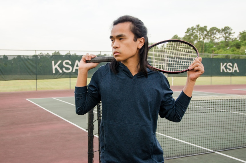Model Wearing Public Rec Politan Hoodie And Standing Holding Tennis Racquet On Shoulder