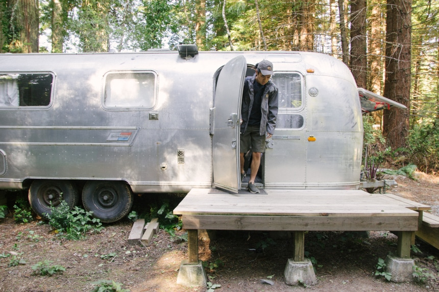 Man coming out of Airstream camper in the woods while wearing Carhartt Odessa Cap Force Delmont Tee Shoreline Jacket and Rugged Flex Cargo Shorts