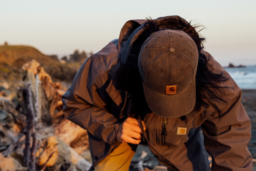 Man looking at driftwood on a beach while wearing Carhartt Shoreline Jacket Odessa Cap and Rugged Flex Rigby Dungaree