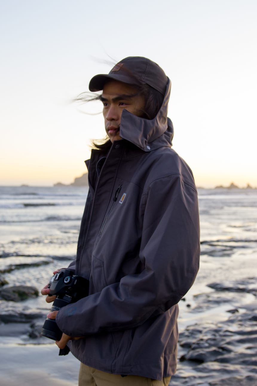 Man on beach next to ocean holding camera in the wind while wearing Carhartt Shoreline Jacket and Rugged Flex Dungaree