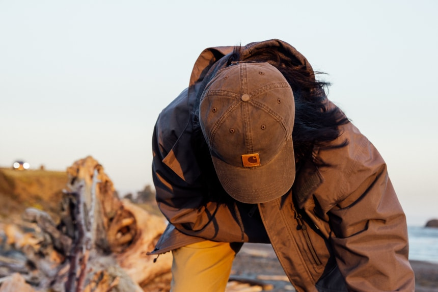 Man on beach picking up driftwood wearing Carhartt Shoreline Jacket Odessa Cap and Rugged Flex Rigby Dungaree