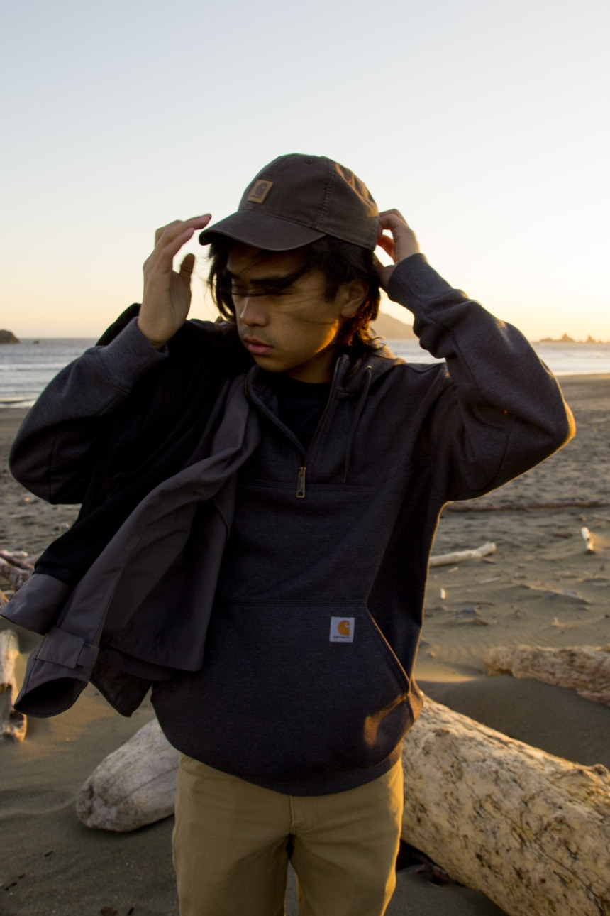 Man on beach wearing Carhartt Odessa Cap Rugged Flex Rigby Dungaree and Rain Defender Paxton Zip Mock Sweatshirt
