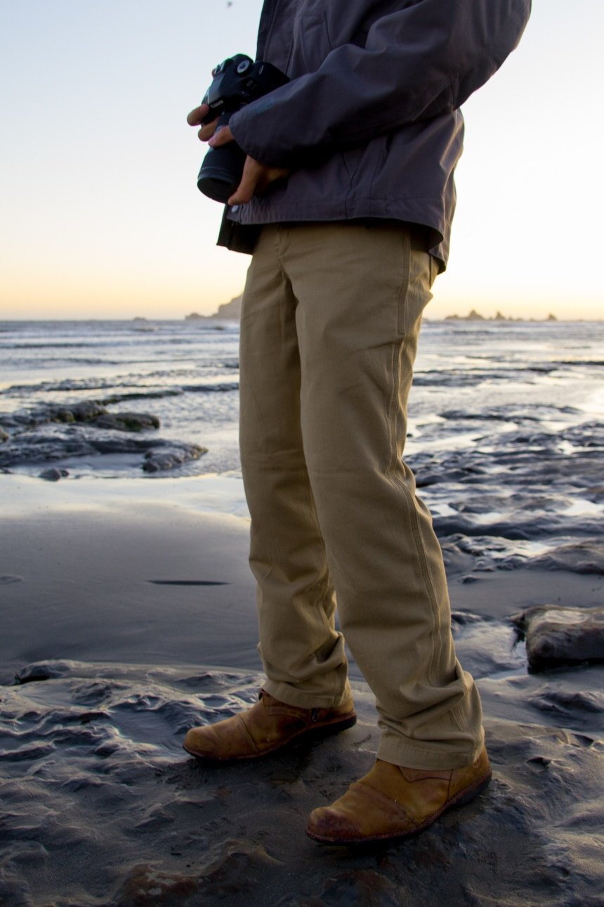 Man on seashore holding camera wearing Carhartt Shortline Jacket and Rugged Flex Rigby Dungaree