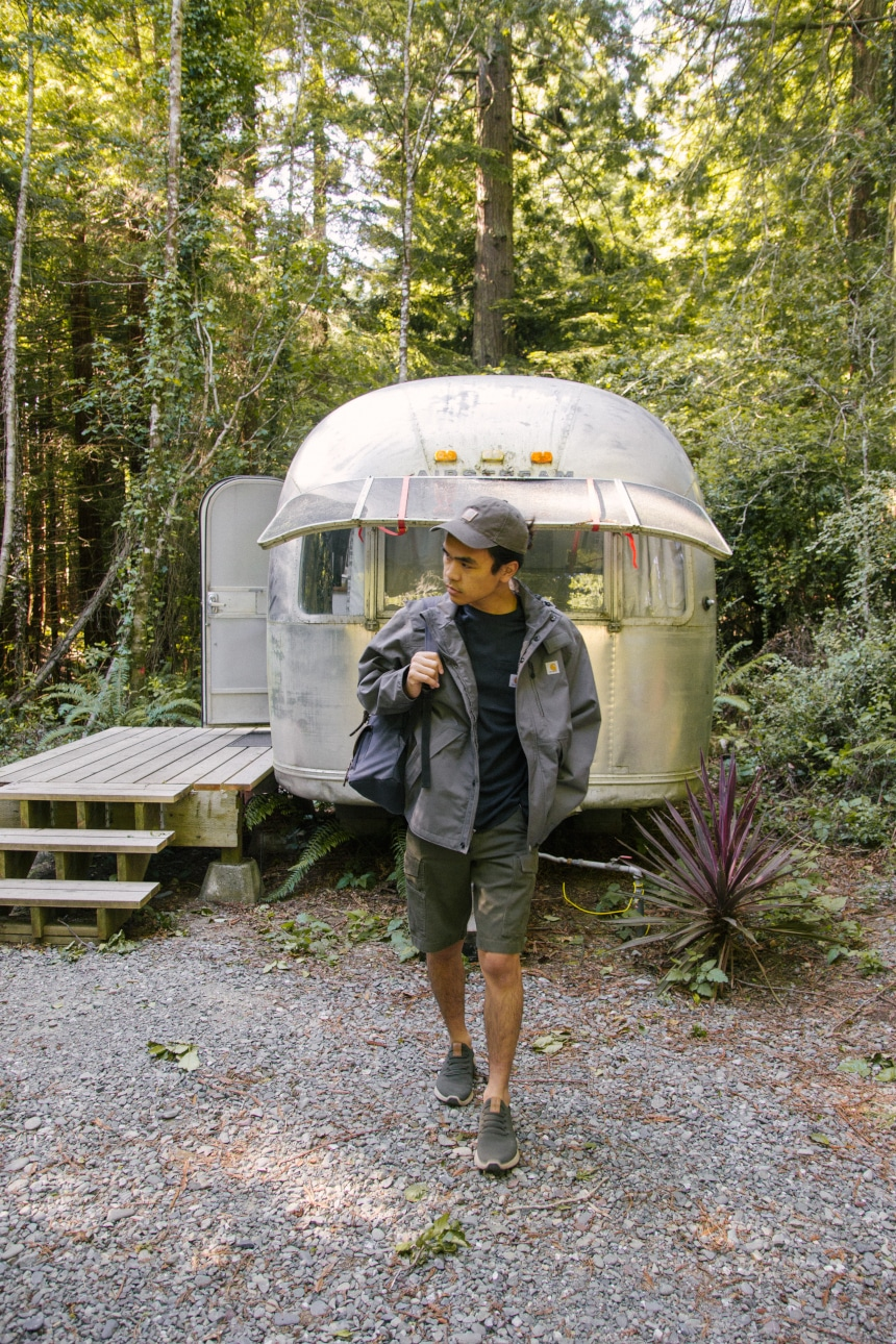 Man walking away from Airstream camper in the woods wearing backpack and Carhartt Odessa Cap Shoreline Jacket Rugged Flex Rigby Cargo shorts and Force Delmont Tee
