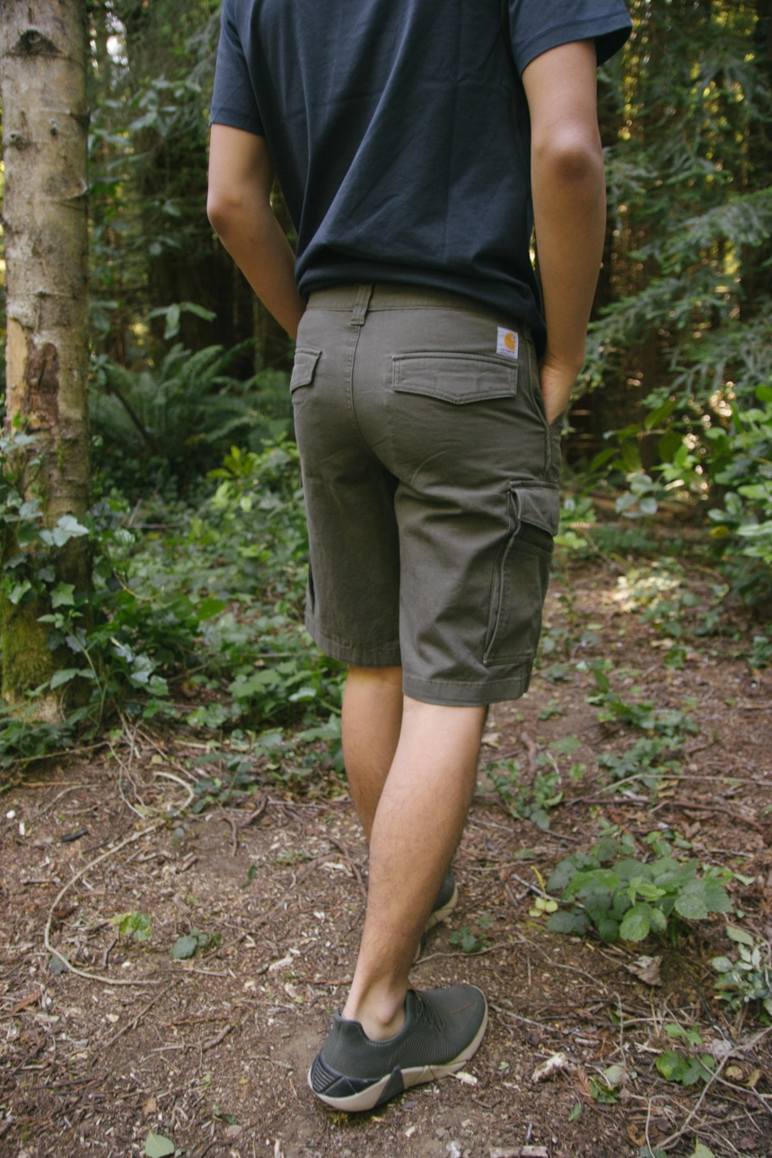 Man walking though forest wearing Carhartt Force Delmont Tee and Rugged Flex Rigby Cargo Shorts backward facing