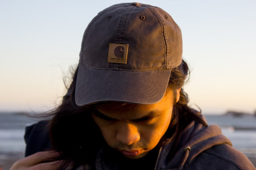Man with long hair on a beach wearing Carhartt Odessa Cap b