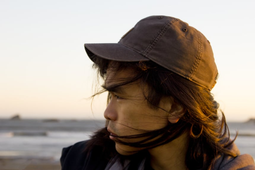 Man with long hair on beach wearing Carhartt Odessa Cap