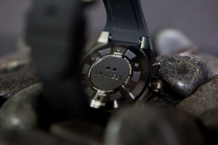 TW Steel CEO Tech watch back facing with logo propped on top of black stones on black background c