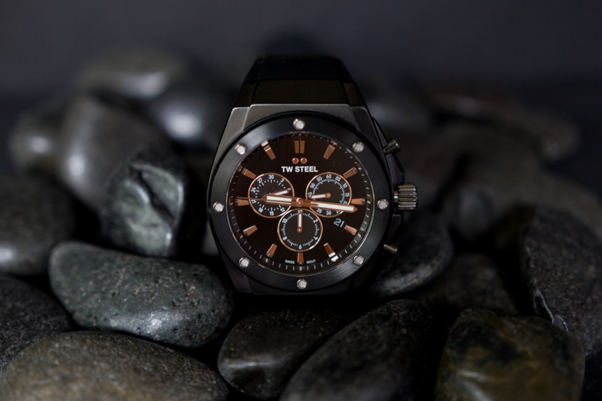 TW Steel CEO Tech watch propped up against black stones on black background e