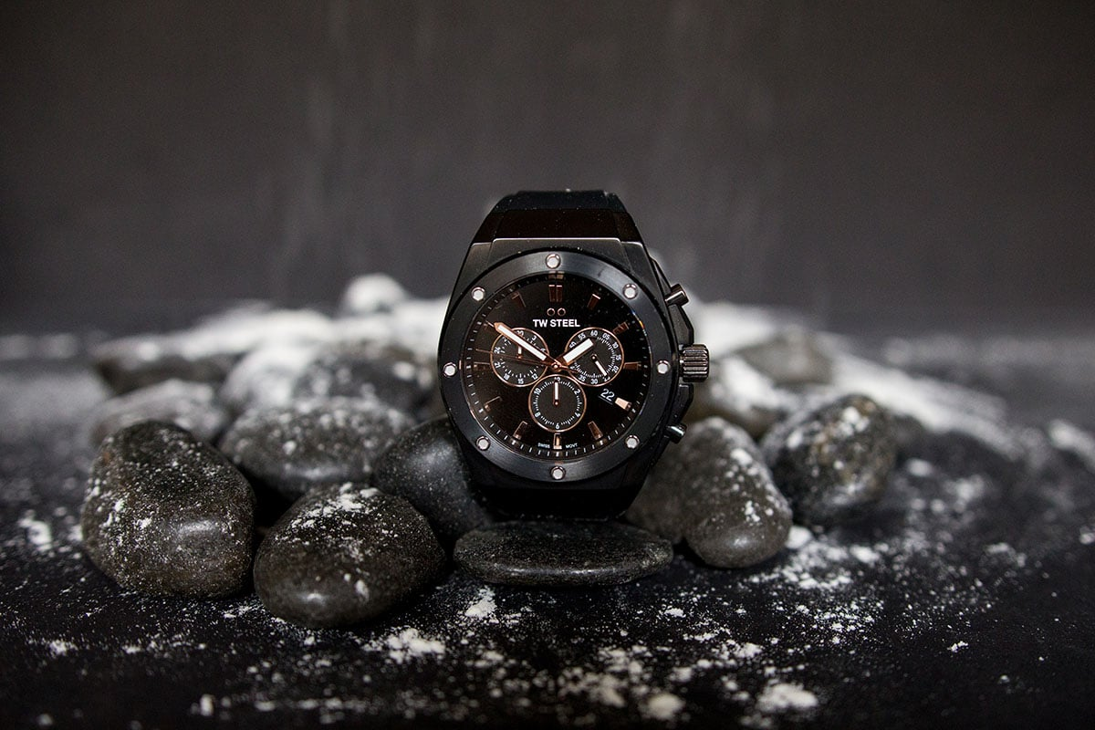 TW Steel CEO Tech watch propped up against black stones with snow on black background a