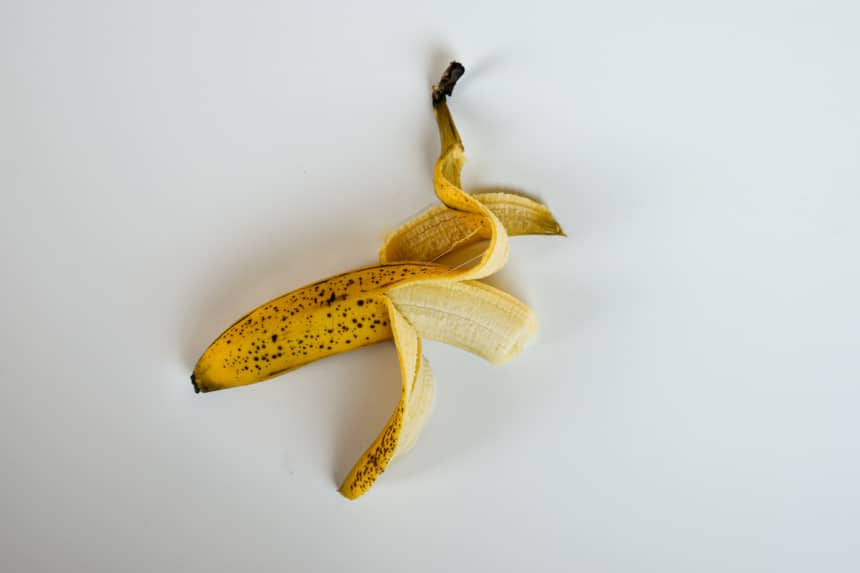 Bruised Banana Half Unpeeled on White Background