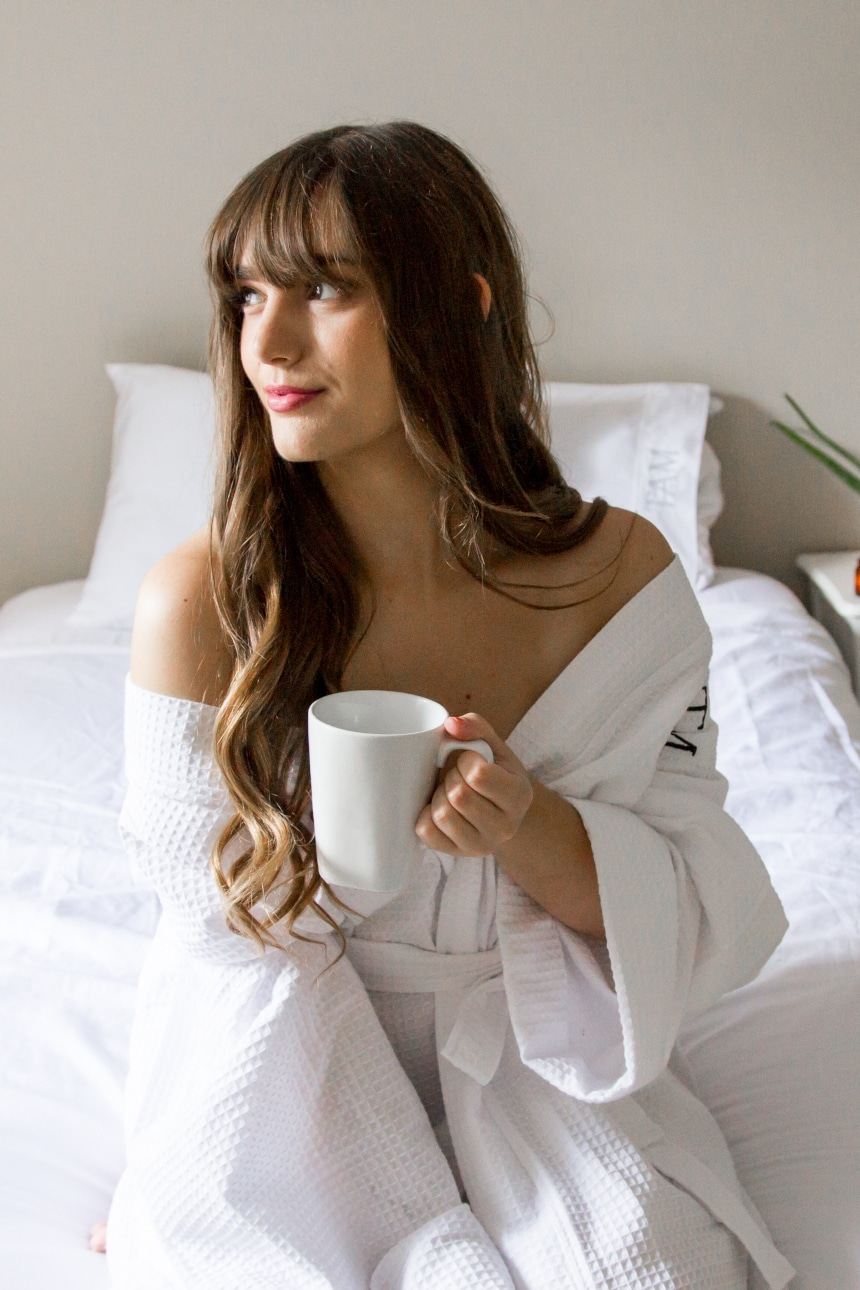 Female model wearing Luxor Linens Lakeview Signature Egyptian Cotton Spa Robe while holding a coffee and looking into the distance