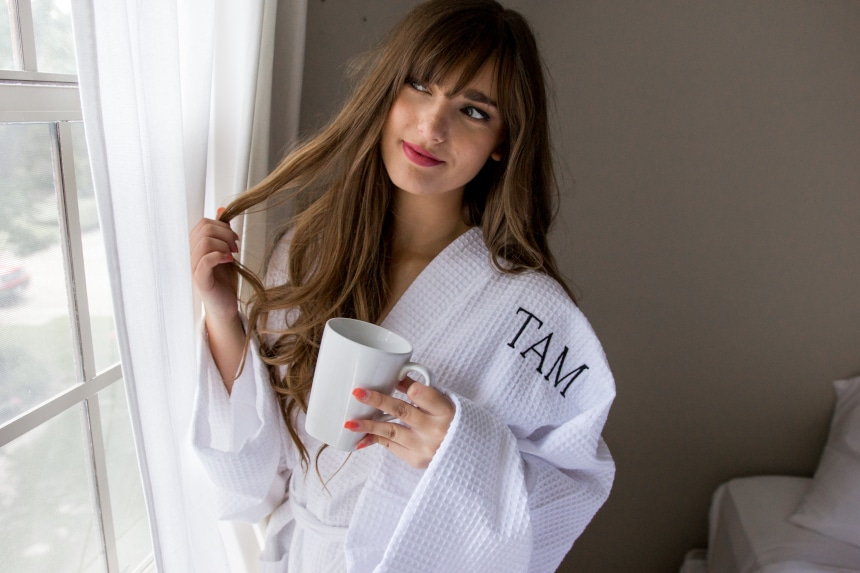 Female model wearing Luxor Linens Lakeview Signature Egyptian Cotton Spa Robe while holding a coffee and looking out the window and twirling her hair