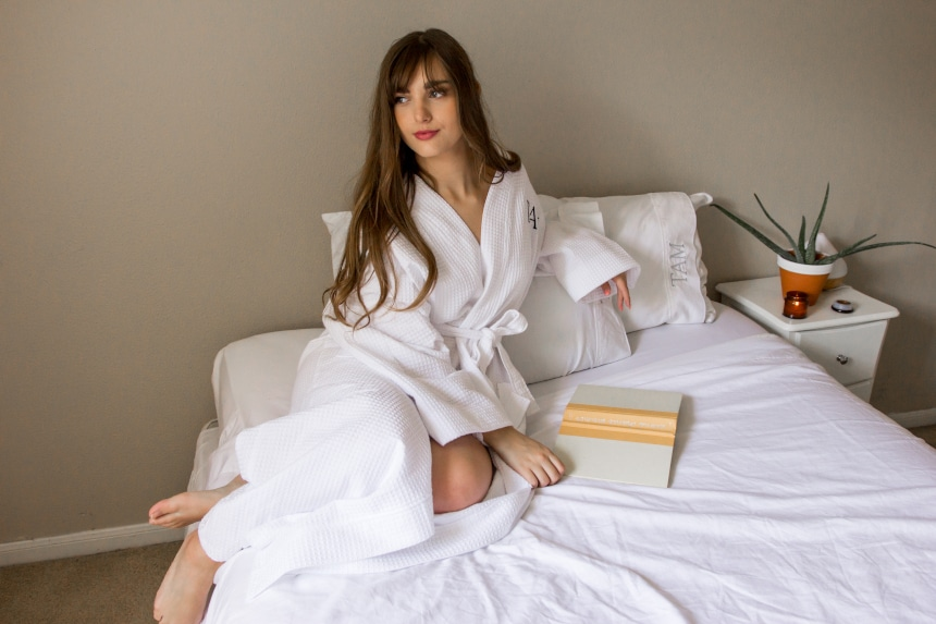Female model wearing Luxor Linens Lakeview Signature Egyptian Cotton Spa Robe while lying on bed with a book